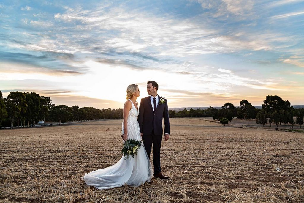 bride and groom sunset in field